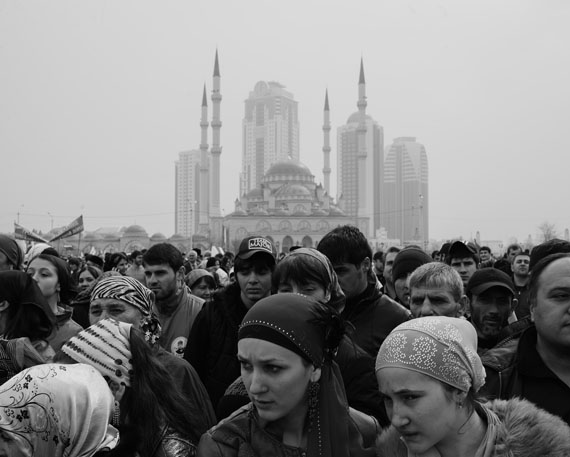Republic of Chechnya, Russia, 03/2013. A group of pro-Kadyrov activists in the city's main square celebrating the 10th Constitution Day. In the background are the Central Mosque and the Grozny City skyscrapers, the main symbol of the reconstruction of Grozny and Chechnya thanks to the efforts of President Kadyrov and the money provided by Moscow. Grozny.g to transform it into one of the region's main tourist destinations. Karachoi. © Davide Monteleone /VII for Carmignac Gestion Photojournalism Award