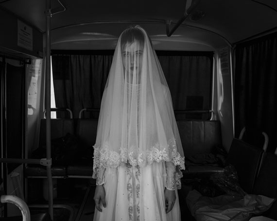 Republic of Chechnya, Russia, 03/2013. Rada, 14, trying on a wedding dress designed by her sister inside a bus during a rehearsal for a movie on the Chechen deportation. As in many other Muslim countries, child brides were very common in Chechnya. Although President Kadyrov strongly promotes a merger of Chechen tradition and Islamic law, the Russian federal government recently forced him to publicly condemn the practice of child marriage, which is illegal throughout the Russian Federation. Shatoy. © Davide Monteleone /VII for Carmignac Gestion Photojournalism Award