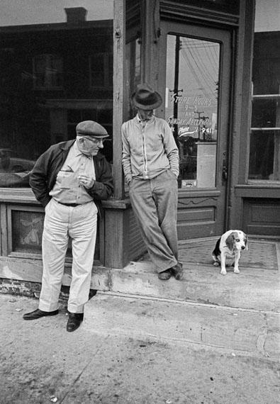 Zwei Männer und ein Hund vor dem Schaufenster einer kleinen Stadt entlang der Autobahn, Iowa, 1963© Thomas Hoepker / MAGNUM PHOTOS