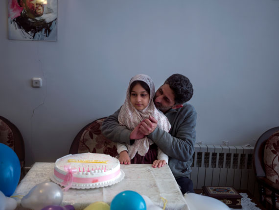 "Ali, a war veteran, holding his daughter Hadis, on her 8th birthday party. He fought on the fronts of the Iran-Iraq war for seven years, joining as a volunteer when he was 16. "" My body has returned home,"" he says, ""but my spirit stayed behind.""  © Newsha Tavakolian"