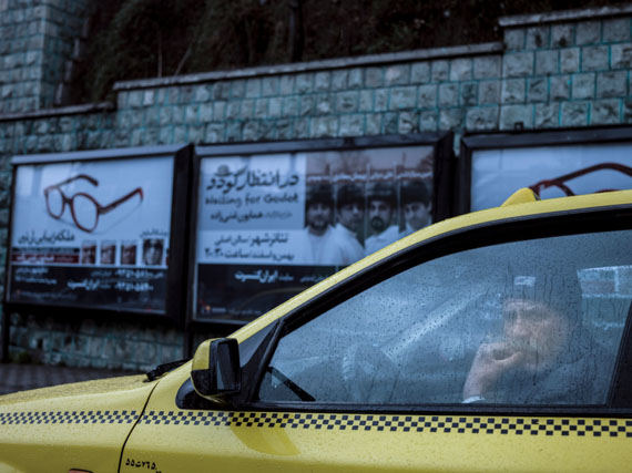 A taxi driver in his car on a rainy day. Behind him a poster of an upcoming performance of Samuel Beckett's play 'Waiting for Godot'. © Newsha Tavakolian