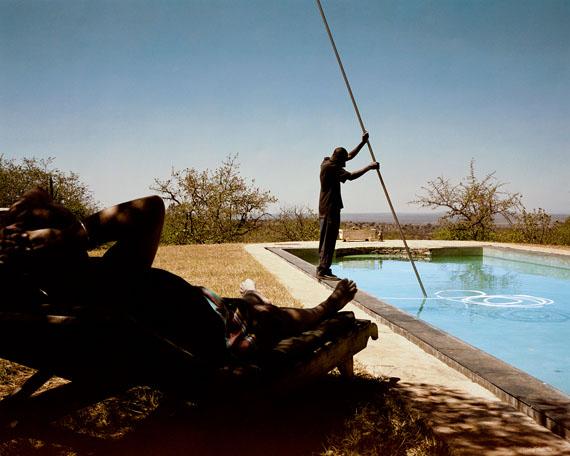 Guillaume Bonn: Ein Gärtner reinigt am Wochenende den Pool während ein Gast seines Arbeitgebers ein Sonnenbad nimmt. Aus der Serie Silent Lives, 2009 – 2011Lucia Pigmentprint auf FibaPrint Ultra Smooth Gloss  Archival Paper, 285 g/qmAuflage 7+2 AP