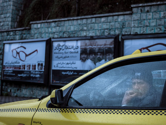 "A taxi driver in his car on a rainy day. Behind him a poster of an upcoming performance of Samuel Beckett's play ""Waiting for Godot"".