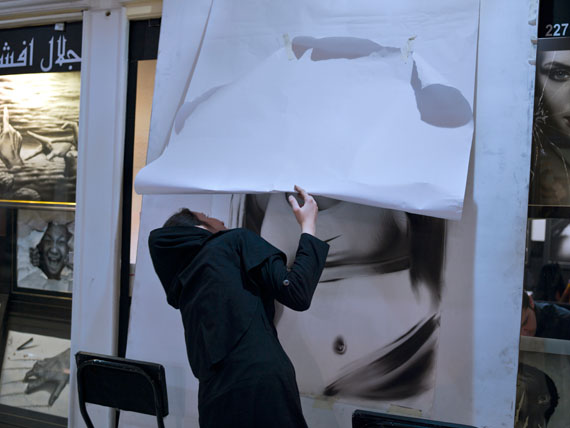A young woman tries to sneak a peek of a drawing of a woman covered by white paper in Qaem Mall,under Iran's Islamic laws showing women's bodies in public is forbidden. © Newsha Tavakolian for the Carmignac Foundation