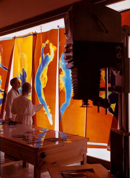 Ganzkörper-Farbfotogramme auf Positivfilm-Bahnen hängen vor einer Leuchtwand in der Großbilddiastelle der Wolfener Filmfabrik ORWO. Die Fotogramme ('Harlekin und Colombine', 1968) entstanden für den Messestand von ORWO auf der Photokina in Köln 1968.© SLUB / Deutsche Fotothek / Schröter, Wolfgang G.