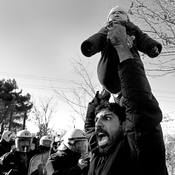 Nikos Pilos: Ein iranischer Migrant demonstriert mit seinem in die Luft gehobenen Kind vor der griechischen Polizei für das Recht, die Grenze zu überqueren.