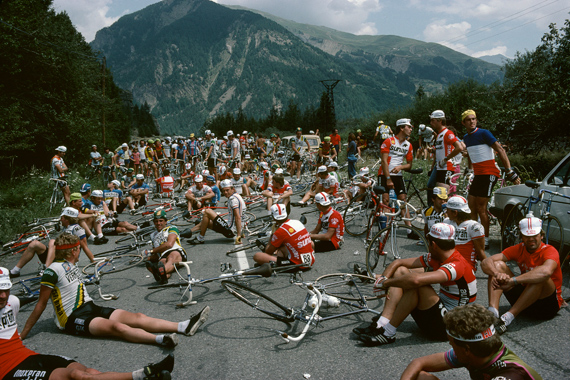 Riders relax whilst the Tour organizers negotiate with farmers on stage 16 to remove their tractors from the road, Tour de France, 1982 © Harry Gruyaert / Magnum Photos