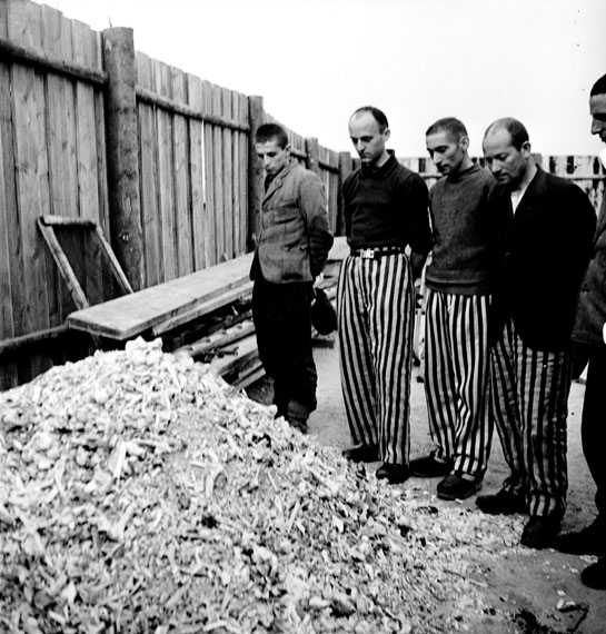 Released prisoners in striped prison dress beside a heap of bones from bodies burned in the crematorium Buchenwald, Germany, 1945© Lee Miller Archives, England 2020All rights reserved. leemiller.co.uk