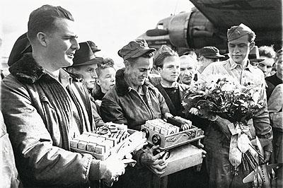 Nach der Aufhebung der Blockade am 12. Mai 1949 bedanken sich die Berliner beim Abschied der ersten Piloten mit Blumen und Süßigkeiten für deren Einsatz. © Henry Ries / The New York Times / DHM