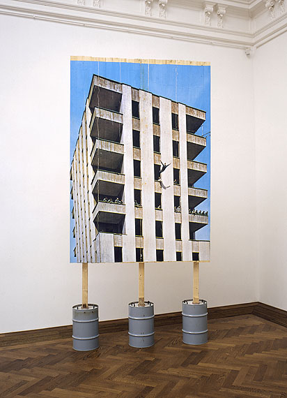 Stefan BurgerLeap into the void under the supervision of a committee of experts, 2006Inkjet-print on wooden wall, concrete, metal drums, 400 x 200 x 80 cm© Stefan Burger