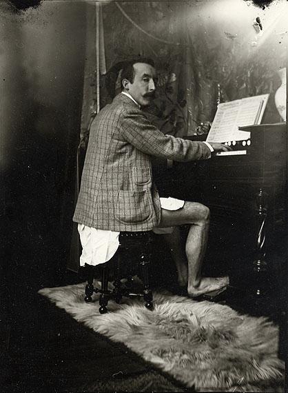 Alphonse Mucha, Paul Gauguin am Harmonium in Muchas Atelier , Paris, um 1893/94Silbergelatine, 24 x 18 cmMucha Foundation, Prag