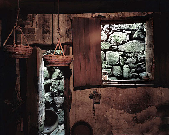"""ROBERT VAN DER HILST: """"Chinese Interiors #100: Rock Wall, Baskets in Wooden Kitchen. Shen'ao Village, Zhejiang Province"""" (2006) Archival pigment print. 46cm x 56cm - Ed. of 15; 67cm x 80cm - Ed. of 10; 110cm x 131cm - Ed. of 5. © Robert van der Hilst. Courtesy of m97 Gallery."""
