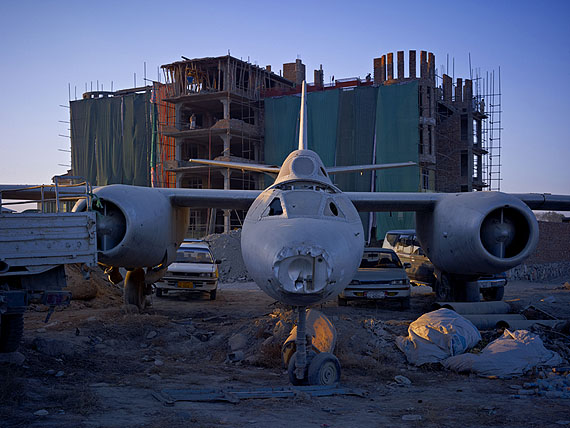 A dumping ground for an abandoned Russian-era bomber that has now been incorporated into the car park of 'Shamshad TV', a new media company supported heavily by American money. Kabul, 201040x53