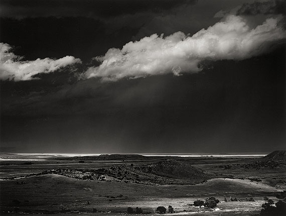 Ansel AdamsSTORM OVER THE GREAT PLAINS FROM CIMARRON, NEW MEXICO. 1960Gelatin silver print, c. 1975. 37,3 x 49,2 cm. Laid down on original cardboard, thereupon lower right signed in pencil. On the reverse of the cardboard photographer's stamp, therein dated and inscribed in black felt-tip pen. Courtesy Villa Grisebach Auktionen