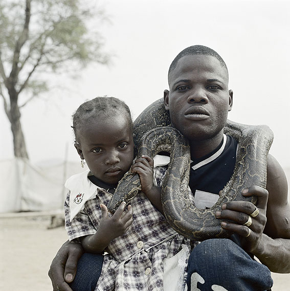 Pieter Hugo, Mummy Ahmadu and a snake charmer with a rock python, Abuja, Nigeria, 2005 From the series The Hyena & Other Men© Courtesy of Stevenson Gallery, Cape Town / Yossi Milo, New York