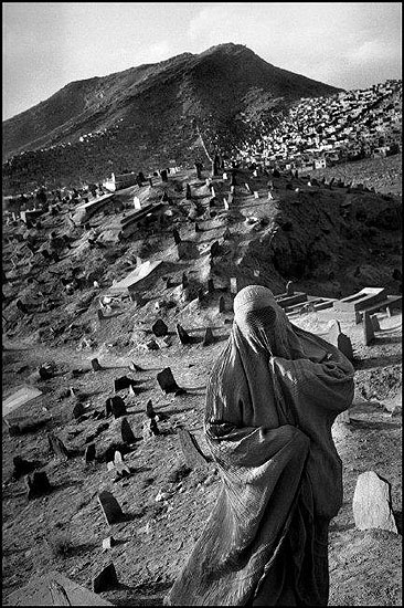 © Abbas / Magnum Photos, AFGHANISTAN. Kabul. A woman in burqah, the full islamic veil, has come to pay respect to the dead at the Shi'ite shrine of Sakhi Jan. 2001.