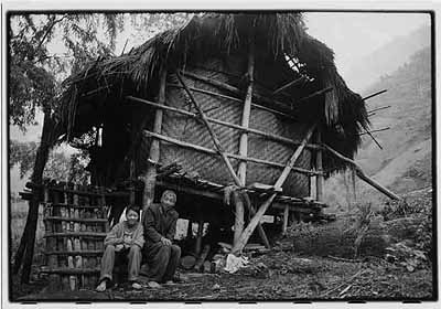 Yunnan, 1998 ©Zhang Xinmin A boy sits with his grandfather next to a traditionally constructed rural dwelling. Children are frequently left with grandparents while their parents earn a living in the cities.