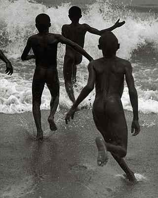 Drei Jungen laufen in die Brandung des Tanganyika-Sees, um 1930 veröffentlicht in: Das Deutsche Lichtbild 1932 Fotografiert von Martin Munkácsi, © Joan Munkácsi. Courtesy ullstein bild