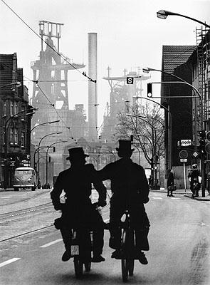 © Walter Vogel, Schornsteinfeger unterwegs auf der Kaiser-Wilhelm-Straße, im Hintergrund die August-Thyssen-Hütte, Duisburg-Bruckhausen, 1965