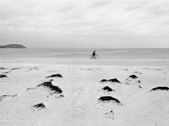 Kurt Kaindl: Der Radfahrer geht am Strand der Halbinsel Priwall an genau jener Stelle, an der früher der Eiserne Vorhang in die Ostsee hineinreichte, die Halbinsel Priwall war auf der Landseite durch den Eisernen Vorhang getrennt