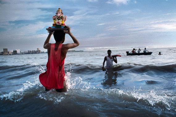 """Mumbai, 1993. Ein Gläubiger trägt während des rituellen Eintauchens am Chowpatty-Strand eine Ganesha-Staute ins Wasser des Arabischen Meers.""""aus Indien (Prestel Verlag, 2015)""""© Steve McCurry"""
