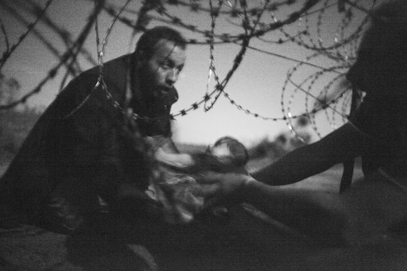 A man passes a baby through the fence at the Hungarian-Serbian border in Röszke, Hungary, 28 August 2015. © Warren Richardson, Australia