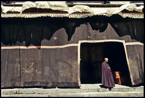 """After morning prayers, a lone monk stands in a doorway leading from the main sanctuary at Sakya Monastery,"" 2007 © Marissa Roth"
