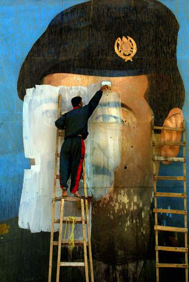 Carolyn Cole: An image of Saddam Hussein, riddled with bullet holes, is painted over by