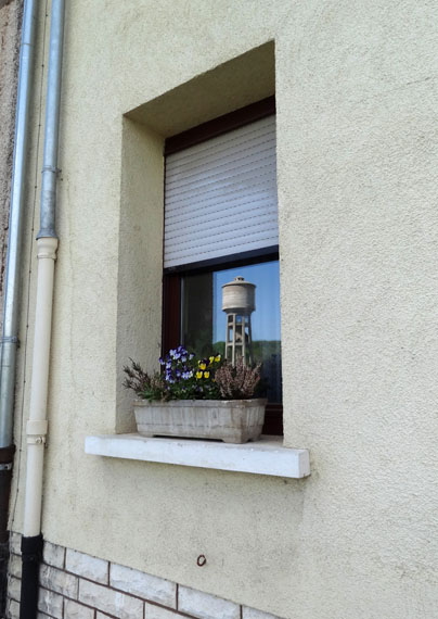 Dudelange. The reflection of the CNA's water tower in the window of a private home. A window that holds the image of a reservoir that contains images of people: an image can contain much more than what it shows. © Gea Casolaro, 2013