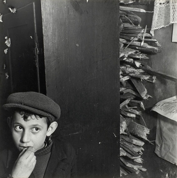 Roman Vishniac: Boy with kindling in a basement dwelling, Krochmalna Street, Warsaw, ca. 1935-38