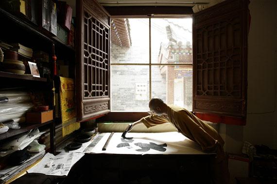 Der Mönch Shi Yongzeng ist ein Meister der Kalligrafie. Mit einem dicken Pinsel zeichnet er auf Reispapier.© Sabine Kress