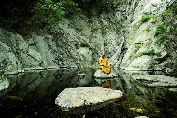 Shaolin-Mönch Shi Yankai wählt für seine Übungen des Shaolin-Qigong immer ruhige Plätze in der Nähe des Klosters aus. Mit ein paar Sprüngen erreicht er den Felsen in der Mitte des kleinen Sees. © Sabine Kress