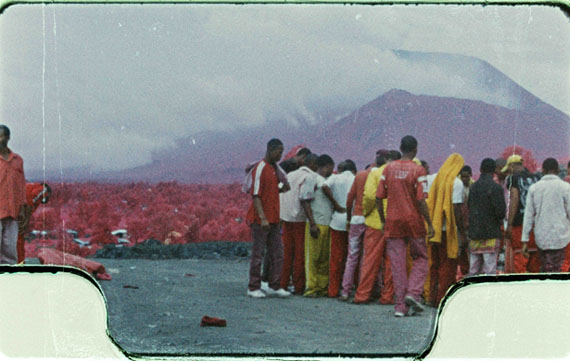 Richard Mosse, The Enclave (still), 2012. 16mm color infrared film transferred to HD video. Filmed in Eastern Congo. Citizens of the city of Goma crowd around the corpses of soldiers from the Congolese national army (FARDC) killed defending the city from the M23 rebel advance. M23 rebels took control of Goma on 19th November 2012.