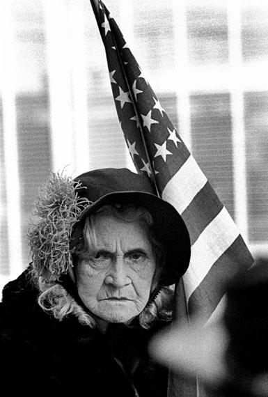 Eine alte Dame mit der amerikanischen Flagge während einer Fourth-of-July-Parade in der Innenstadt, San Francisco, 1963© Thomas Hoepker / MAGNUM PHOTOS