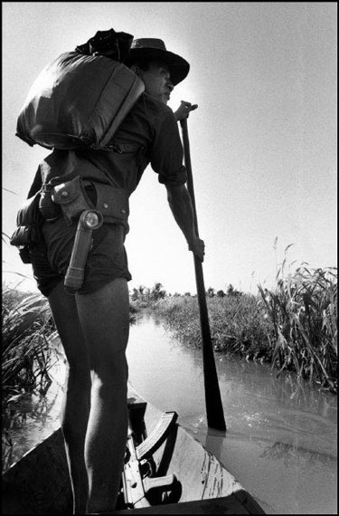 A Vietcong (pro-Communist guerrilla), armed with a Kalashnikov gun, on the move in