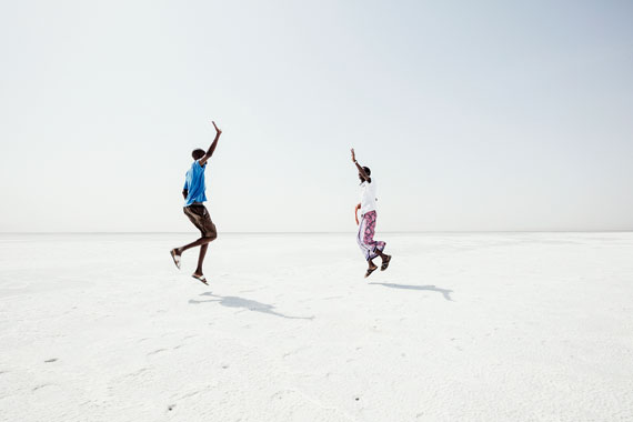 Assal, Salt Plain. The white surface of the Salt Lake. Ali meets his friend Mohamed who also works as a guide for tourists in the Danakil. Happy to meet again, they improvise a Keke dance.© Andrea Frazzetta