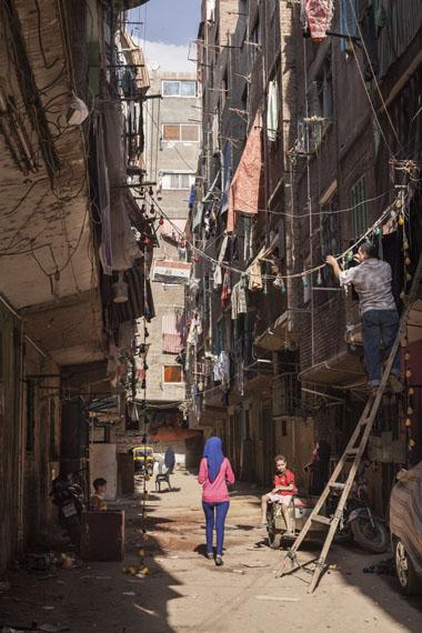 Amélie Losier: Strassenszene mit junger Frau, Kairo, 2014