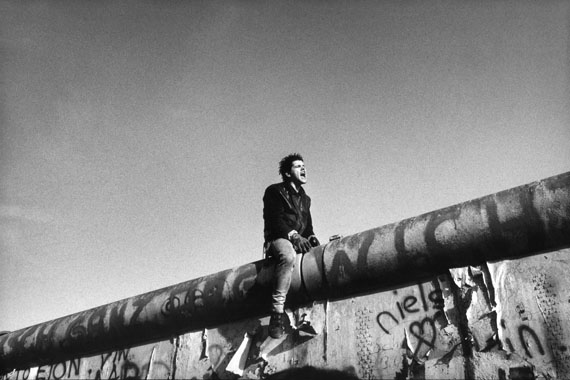 Between the Brandenburg Gate and Potsdamer Platz, a young man sits on the wall between East and West Berlin. West Berlin, Germany, November 11th, 1989