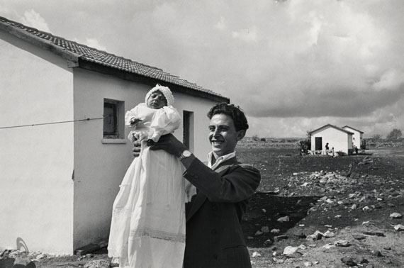 Man holding the first baby born in the settlement of Alma, Israel, 1951© Chim (David Seymour)  Magnum Photos  Courtesy Chim Estate