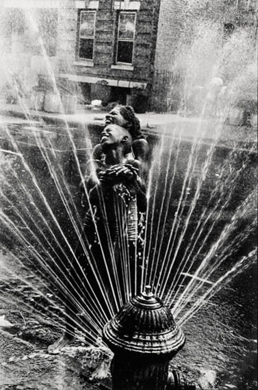 Lot 555Leonard Freed (1929-2016)THE FIRE HYDRANTS ARE OPENED DURING THE SUMMER HEAT, HARLEM, NY, 1963silver gelatin print, printed later, image size 330mm x 220mProvenance: Magnum PhotosEstimate: £300-£350Click to see the image