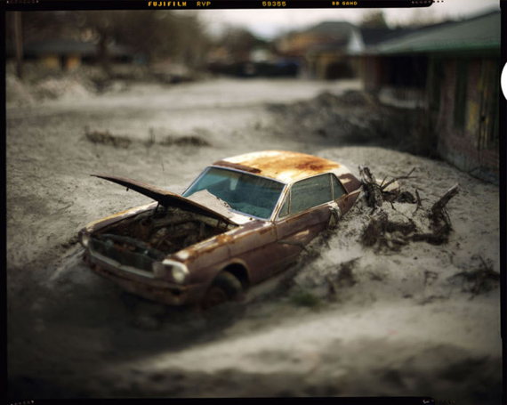TRACES: KATRINA – A lone Ford Mustang, near the 17th St canal, covered in sand after the levees broke. (Speed Graphic) © David Burnett