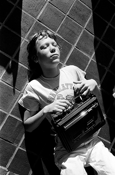 New York, New York, USA: Teenage boy listens to his radio while lying on the cement playgound, 1976Vintage silver gelatin print, 21,5 x 14 / 25,2 x 20,2 cm - vintage © Stephen Shames, Courtesy Galerie Esther Woerdehoff