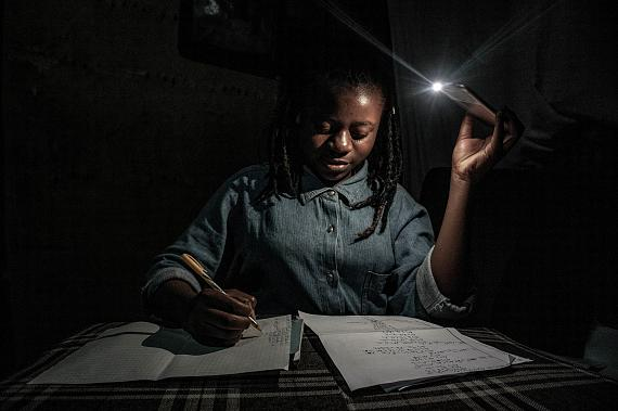 Goma, Democratic Republic of Congo, April 27-28, 2020. With schools closed during Congo's period of confinement, and the city implementing regular power cuts, my 13-year-old sister Marie studies at home by the light of a mobile phone. © Arlette Bashizi for Fondation Carmignac