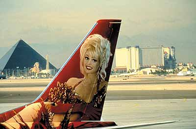 © Lauren Greenfield,The image of Aki, the star showgirl of the Stardust Hotel, on a tail of an airplane, Las Vegas, Nevada.