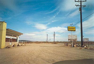 William Eggleston. Untitled, (Yellow Market Sign and Parking Lot), 1999-2001 ©Eggleston Artistic Trust