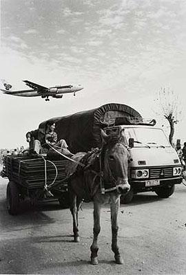Wu Jialin, Kunming, Yunnan 1997, »Fuhrwerk, Lastwagen und ein zur Landung ansetzendes Flugzeug«; © fotoe.com