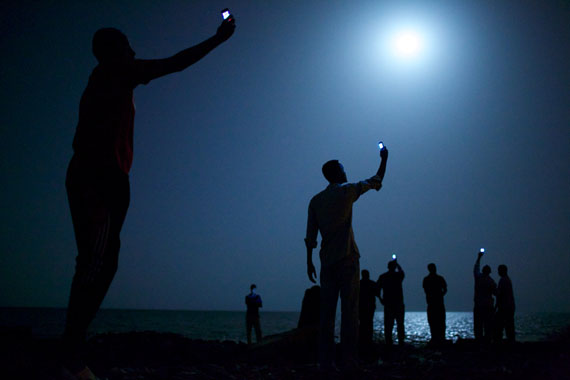 John Stanmeyer, USA, VII for National GeographicWorld Press Photo of the Year 201326 February 2013, Djibouti City, Djibouti: African migrants on the shore of Djibouti city at night, raising their phones in an attempt to capture an inexpensive signal from neighboring Somalia—a tenuous link to relatives abroad. Djibouti is a common stop-off point for migrants in transit from such countries as Somalia, Ethiopia and Eritrea, seeking a better life in Europe and the Middle East.