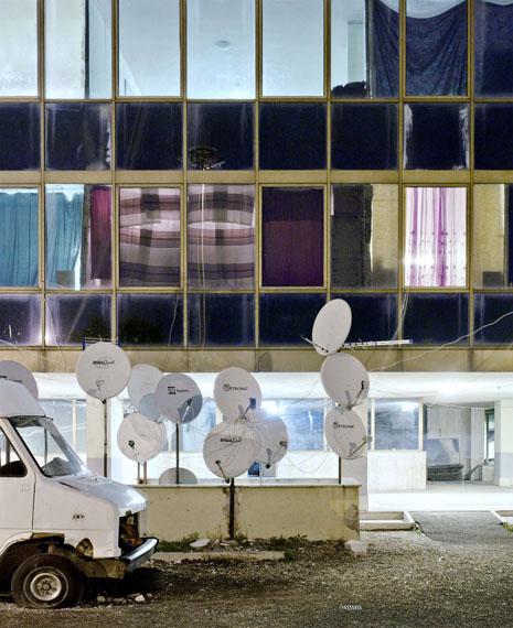"""Eva Leitolf: aus """"Postcards from Europe 10/14""""Archivpigemntdruck auf Tecco PFR 295 auf Archivkarton, 83,5 x 68,6 cm, Text.  Ed. 7 + 1 APPfE-3456-IT-281012Palazzo Selam, Rom, Italien 2012 In einem seit 2006 besetzten ehemaligen Gebäude der Universität Rom leben im November 2012 835 zumeist anerkannte Flüchtlinge aus Somalia, Eritrea, Äthiopien und Sudan. Ärzte der Organisation Cittadini del Mondo, die die von der Stadtverwaltung geduldeten Besetzer ehrenamtlich betreuen, stellen bei den Bewohnern wiederholt  Krankheiten fest, die sich auf die unzureichende sanitäre Infrastruktur zurückführen lassen.Laut Angaben der Stiftung Integra/Azione  bräuchten in Rom 6000 Flüchtlinge eine Unterkunft, die Stadt stelle aber nur 2200 von landesweit 3150 eingerichteten Plätzen bereit. Bereits 2011 legt in Deutschland der Anwalt eines somalischen Asylbewerbers nahe, dass die italienischen Behörden mit einer Verelendungsstrategie versuchten, eine Verteilung von Flüchtlingen auf die anderen EU-Staaten durchzusetzen. Am 2. Juli 2012 entscheidet das Verwaltungsgericht Stuttgart dass eine palästinensische Familie nicht nach Italien überstellt werden darf, da ihr dort aufgrund systemischer Mängel des Asylverfahrens menschenunwürdige Behandlung drohe. Das Bundesamt für Migration und Flüchtlinge will die bisherige Rückführungspraxis beibehalten, da Italientrotz Mängel über ein funktionierendes Asylverfahren gemäß den Standards der Europäischen Union verfüge.Pro Asyl, The Living Conditions of Refugees in Italy, Februar 2011; Süddeutsche Zeitung, 9.5.2011; Verwaltungsgericht Stuttgart, Pressemitteilung vom 12.7.2012 (A 7 K 1877/12); Spiegel Online, 13.7.2012; The New York Times, 26.12.2012; Homepage Cittadini del Mondo, 31.12.2012"""