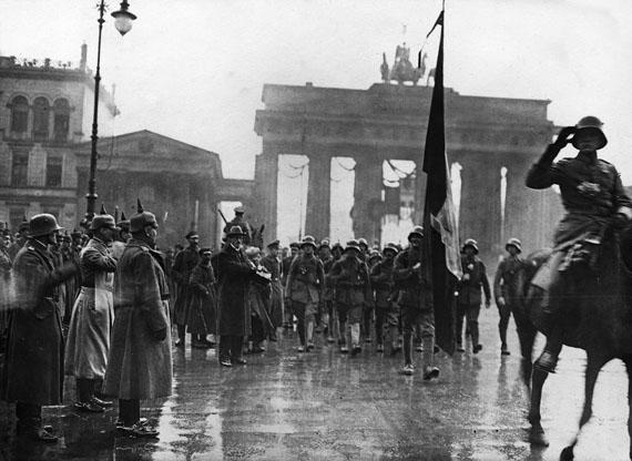 The Guards Ranger Battalion marching past General Lequis, on the left the photographer Walter Girckewith camera, 12/11/1918© Staatliche Museen zu Berlin, Kunstbibliothek – Photothek Willy Römer / Willy Römer