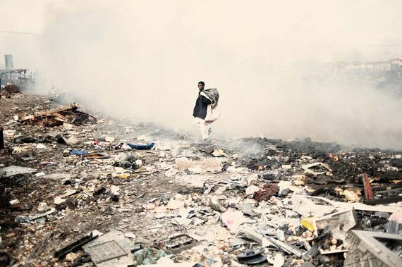 Kai Löffelbein: Africa, Ghana, Accra – Ein Mann durchsucht den Schrottplatz nach alten Elektroschrottteilen.